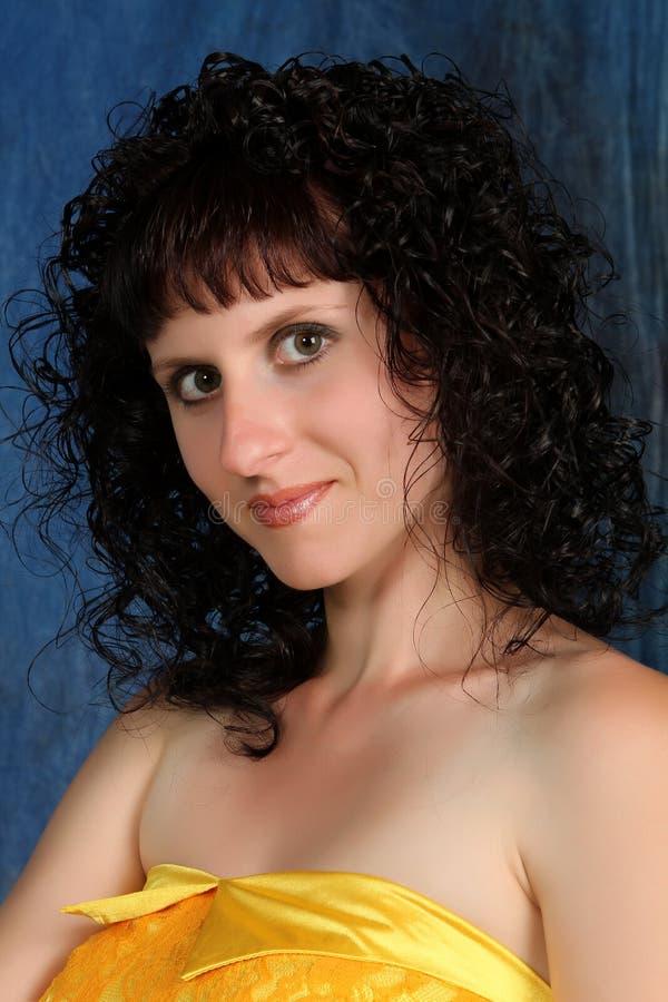 Brunette in einem gelben Kleid auf einem blauen Hintergrund lizenzfreies stockbild