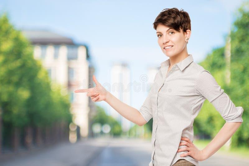 Brunette in einem gestreiften Hemd zeigt seinen Finger lizenzfreie stockfotos