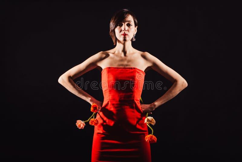 Brunette in einem roten Kleid mit Blumen auf einem schwarzen Hintergrund stockbilder