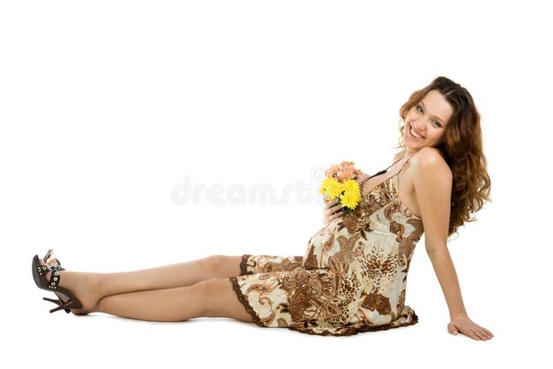 Brunette embarazado sonriente con las flores fotografía de archivo libre de regalías