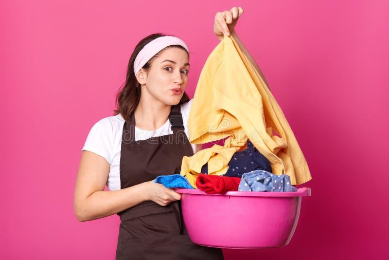 Brunette emotionales Modell wirft voll lokalisiert über heller rosa Hintergrundstellung mit Becken von bunten schmutzigen Einzel stockfotografie