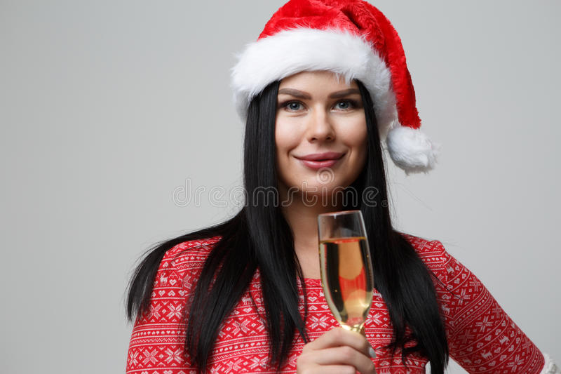 Brunette on empty gray background. Brunette in Santa hat and with champagne on empty gray background royalty free stock photo