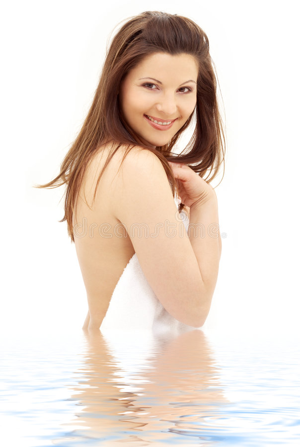 Brunette encantador com a toalha branca na água imagem de stock