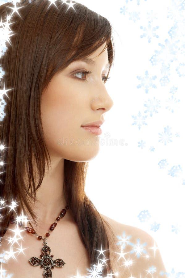 Brunette encantador con la cruz y los copos de nieve imágenes de archivo libres de regalías