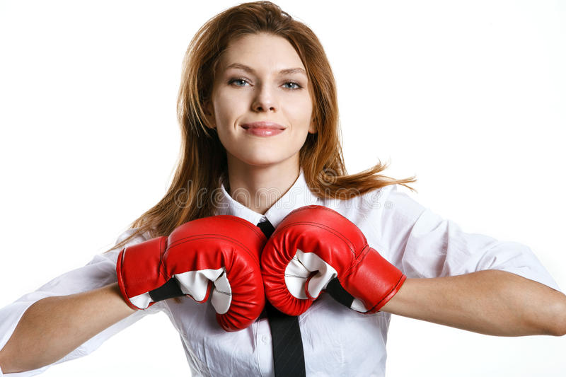 Brunette european woman is ready to kick. Smiling woman with red boxing gloves on a white background stock images