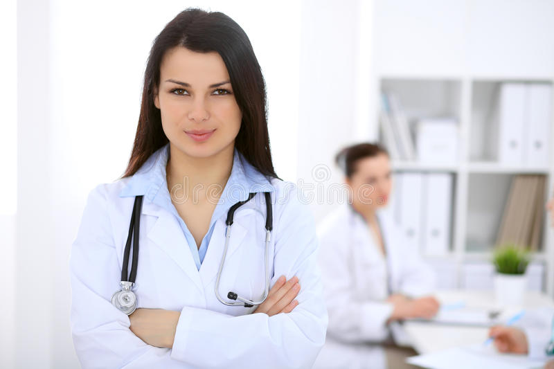 Brunette female doctor on the background of colleagues talking to each other in hospital royalty free stock photos
