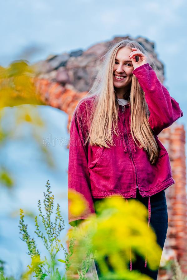 Brunette Female Fashion Model in Countryside Environment with Purple Sweater and Dark Blue Jeans - Sunny Autumn Day stock images