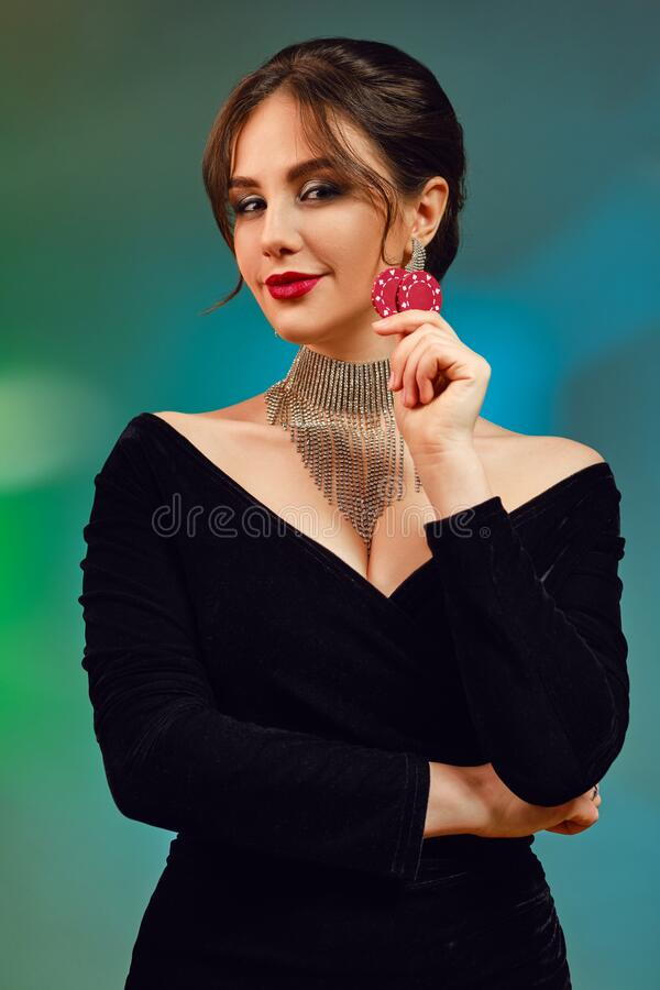 Free Brunette Female In Black Dress, Necklace And Earrings. She Is Smiling, Showing Two Red Chips, Posing On Colorful Stock Images - 179393304