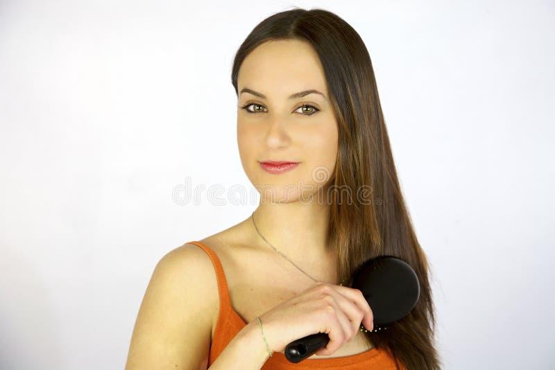 Brunette female model brushing happy her hair stock photos