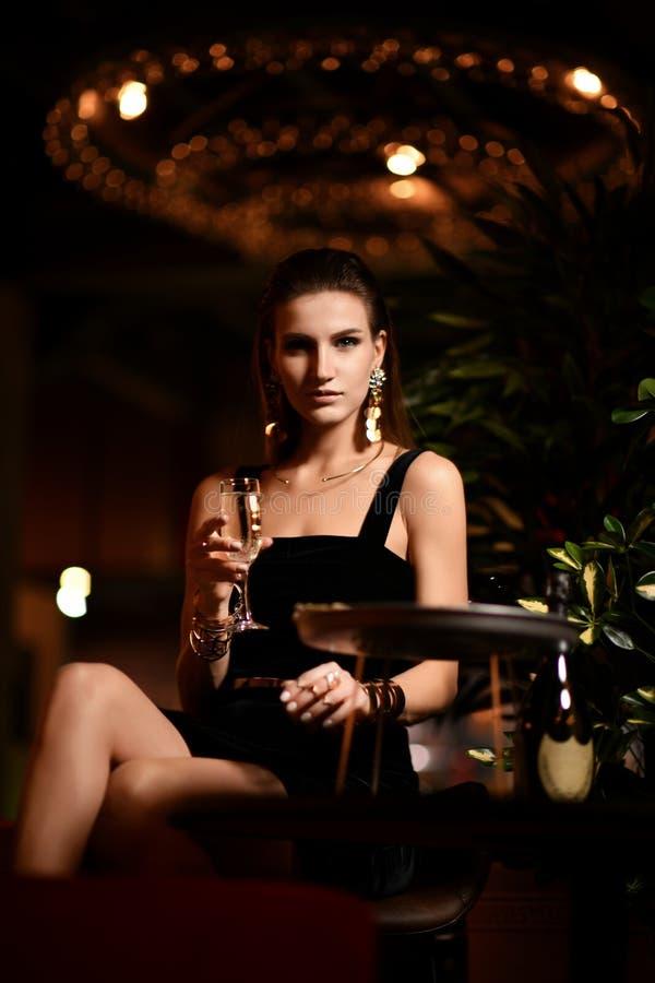 Brunette Frau der schönen sexy Mode in Entspannungstrinkendem Champagnerwein des Barrestaurants stockfotos