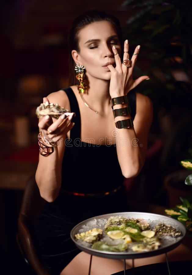 Brunette Frau der schönen sexy Mode im teuren Innenrestaurant essen Austern und lecken einen Finger stockfotos