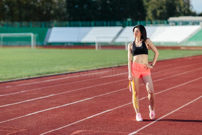 Brunette Frau des glücklichen jungen Sports in der Sportkleidung, die mit gelbem Springseil auf der Stadion instagram Art aufwirf lizenzfreies stockfoto