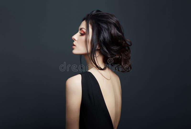 Brunette Frau, die auf dunklem Hintergrund im schwarzen Kleid raucht Erotisches M?dchen lizenzfreie stockfotos