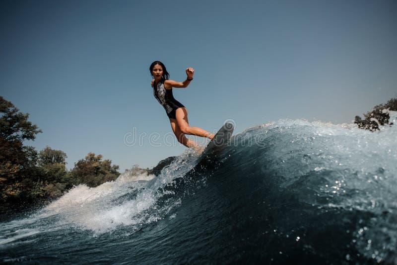 Brunette Frau, die auf ein Surfbrett im Meer surft stockbild