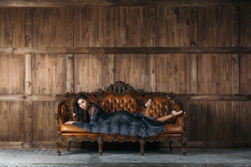 Brunette Frau, die auf ledernes Sofa legt lizenzfreie stockfotos