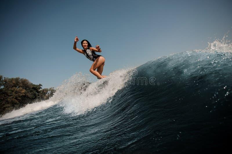 Brunette Frau, die auf Surfbrett im Meer surft lizenzfreie stockbilder