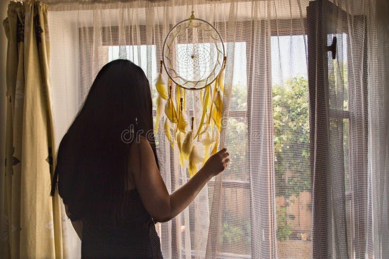 Brunette Frau, die aus dem Fenster heraus schaut, während es sonniger Morgen ist - hintere Ansicht lizenzfreies stockfoto