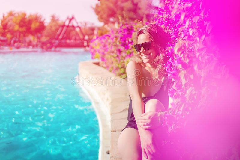 brunette Frau, die am Swimmingpool sich entspannt und lächelt lizenzfreies stockbild