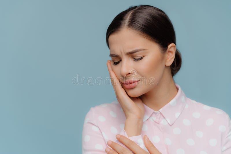 Brunette Frau leidet unter den schrecklichen starken Zahnschmerz, berührt Backe mit der Hand, Bedarf zum Zahnarzt, schließt Augen lizenzfreie stockbilder