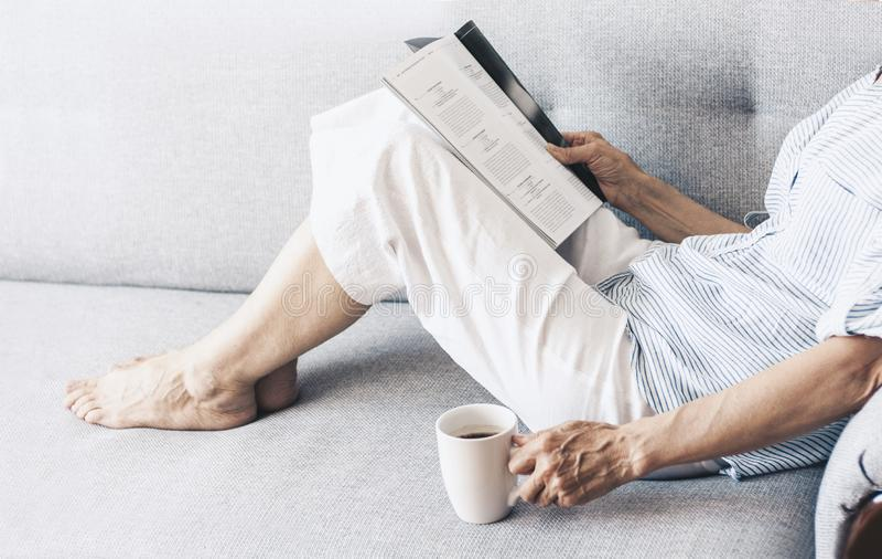 Brunette Frau von mittlerem Alter auf der grauen Sofalesezeitschrift mit Tasse Kaffee stockfotografie
