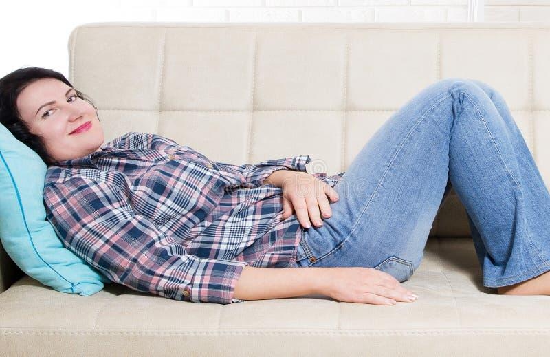 Brunette Frauensofalügen von mittlerem Alter Ein Modell stockbilder