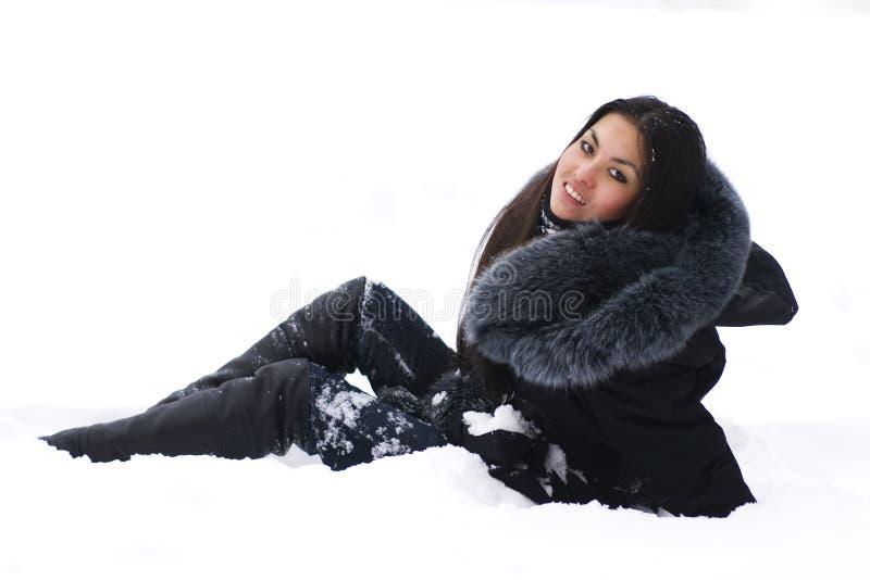 Brunette gai s'asseyant sur la neige photo libre de droits