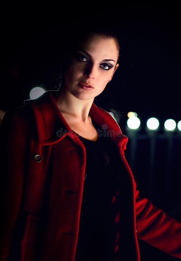 Brunette geht auf eine Nachtstadt lizenzfreies stockbild