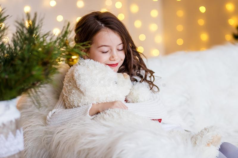 A brunette gilr in front of fur-tree and fireplace with candles and gifts. A girl dreaming. New year`s eve. Christmas . stock photography
