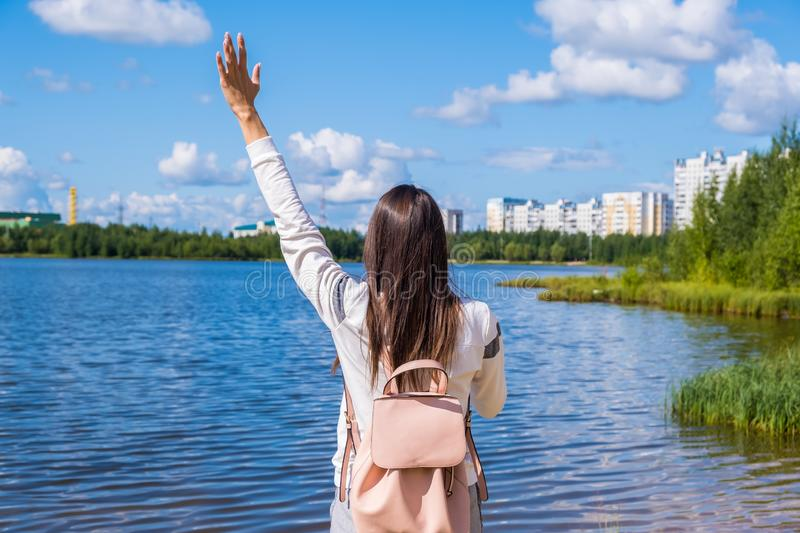 Brunette girl with a backpack enjoys stunning scenic views. Lake and beautiful landscape. Adventure, freedom, lifestyle royalty free stock photo