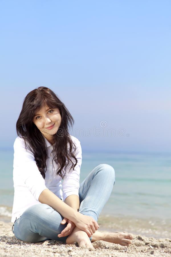 Brunette girl at the beach in spring time. royalty free stock photo