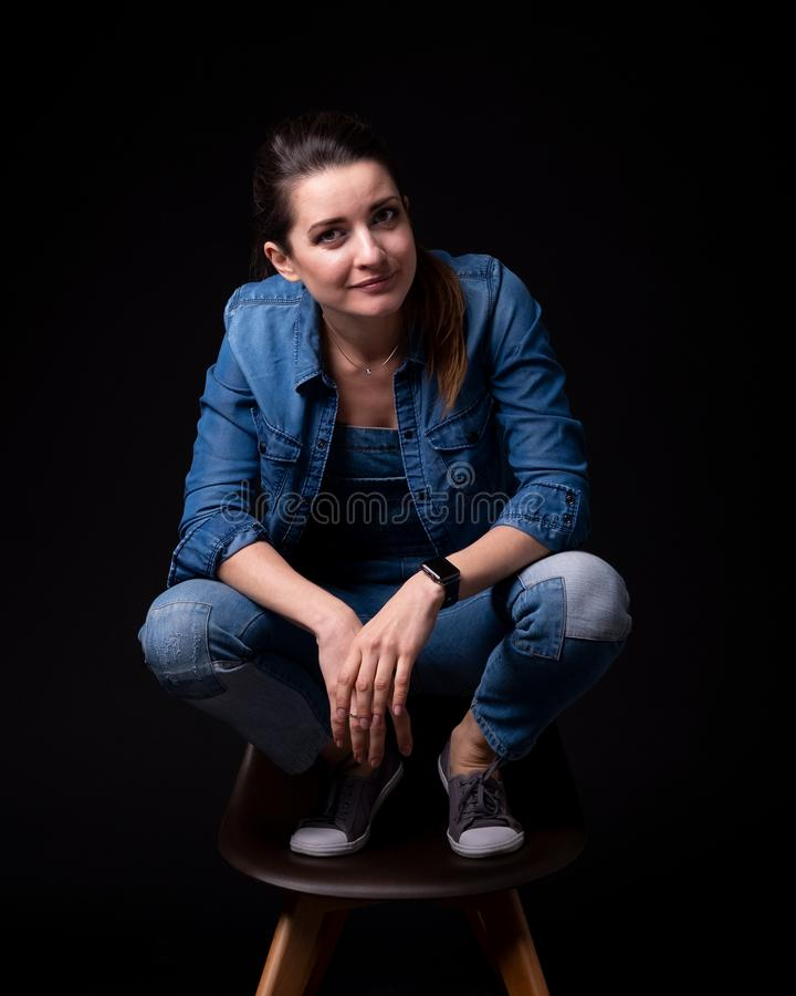 Brunette girl in blue denim jacket and pants. Stands leg up on chair close up on black background royalty free stock photos
