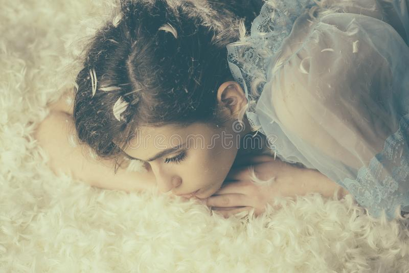 Brunette girl in blue dress lying on downy bed full of feathers, fluff flowing in air. Little angel sleeping on soft. Cloud, coziness concept royalty free stock photography