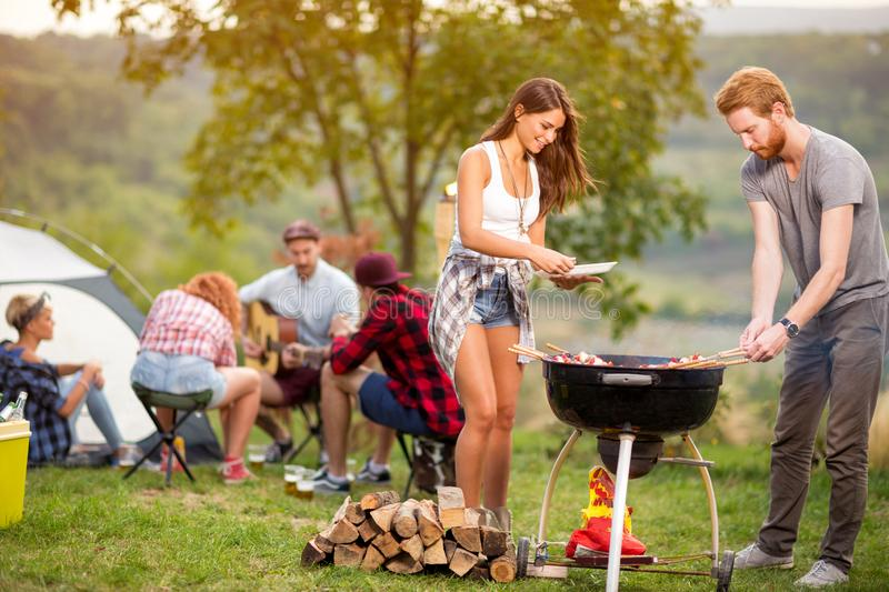 Brunette girl with boyfriend put grill meat in grill royalty free stock photo
