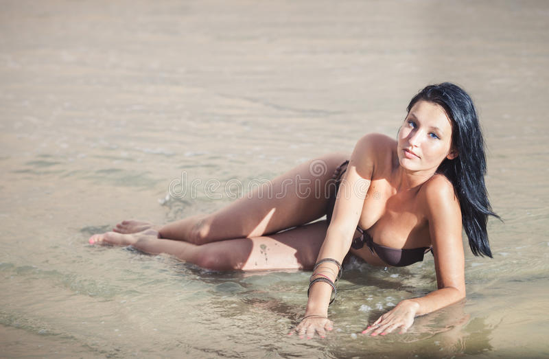 Brunette girl in brown bra. Beautiful brunette young girl in brown bra lying on the white sand with sea water and posing at the camera stock image