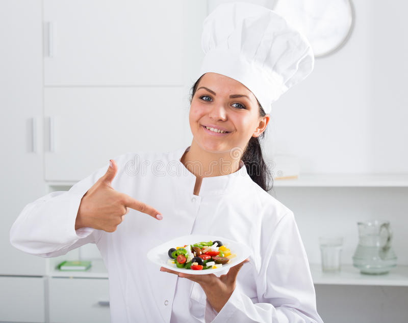 Brunette girl chef and plate with salad. Brunette girl chef showing thumbs up and plate with salad stock photo