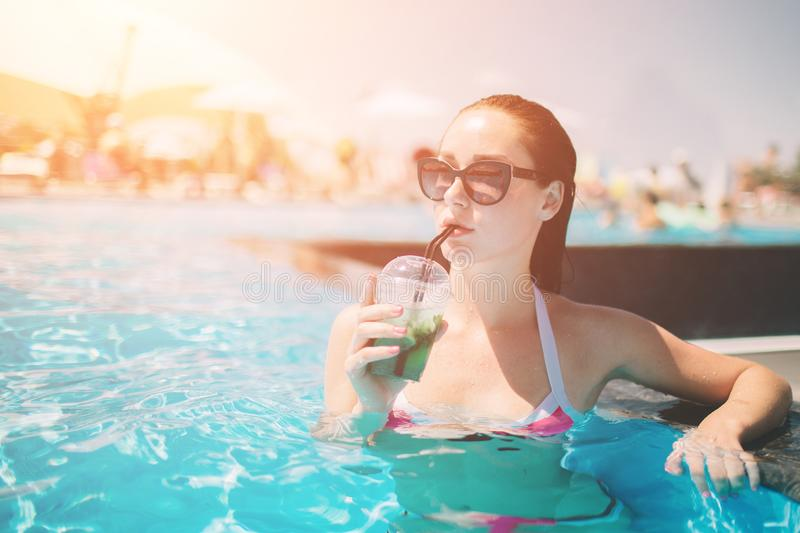 Brunette girl with cocktails relaxing in swimming pool. woman in bikini enjoying summer sun and tanning during royalty free stock images