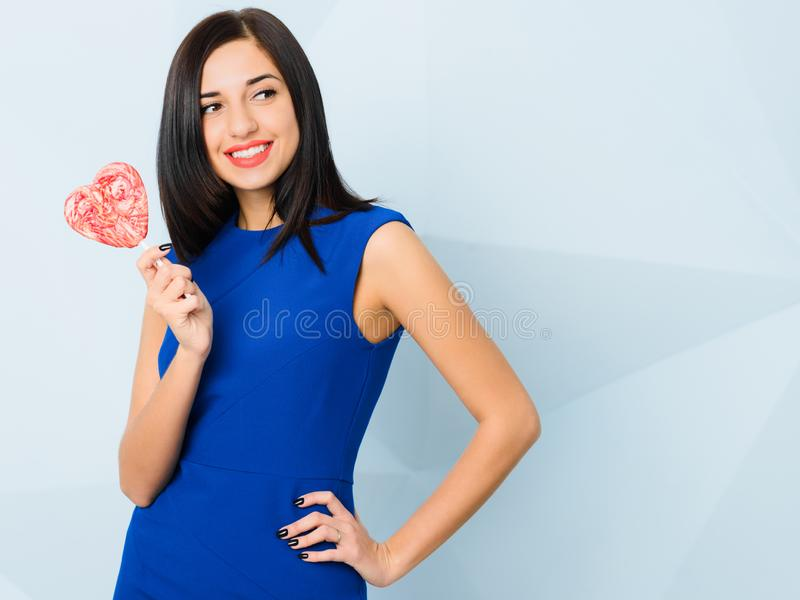 Brunette girl dressed in blue smiling, holding heart shaped red candy in her arm. Saint Valentine`s Day concept stock image