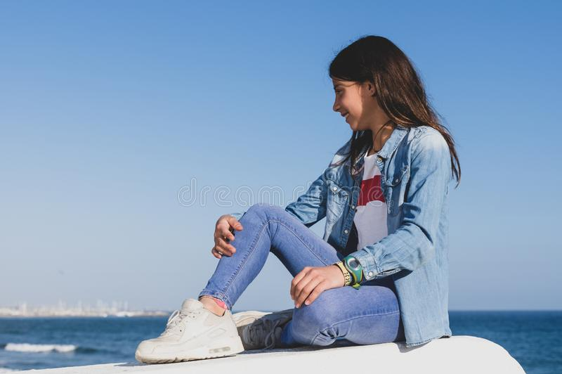 Teenage girl with denim clothes sitting facing the mediterranean sea in spanish coastal town stock photography