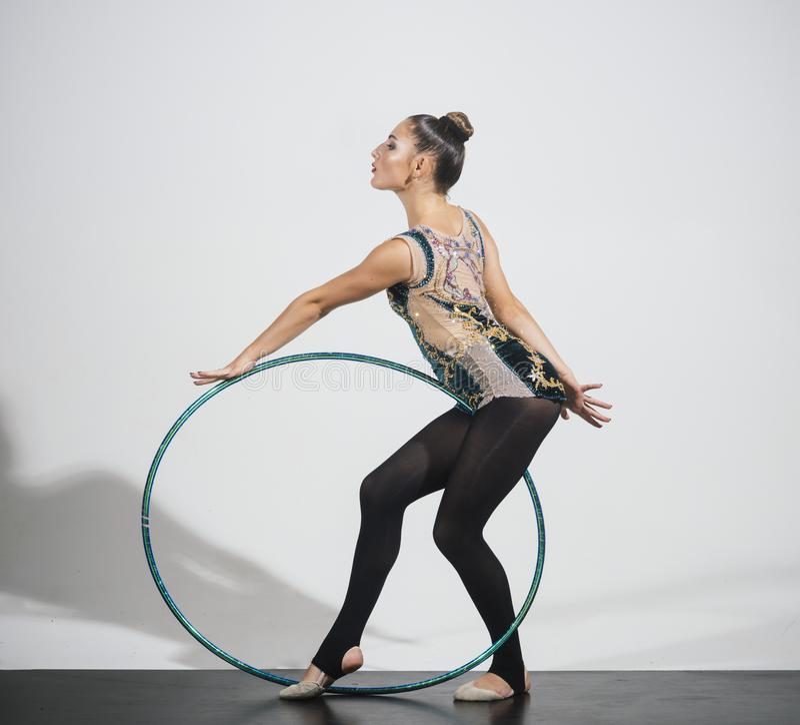 Brunette girl exercising hoola hoop on grey background. Brunette girl exercising hoola hoop on grey background stock photos
