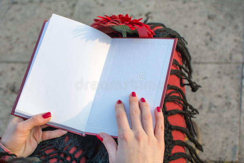 Brunette girl finished reading a book. Outdoors royalty free stock image