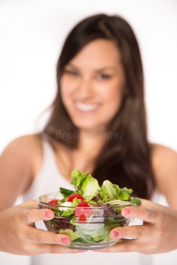 Brunette girl with fresh salad stock image