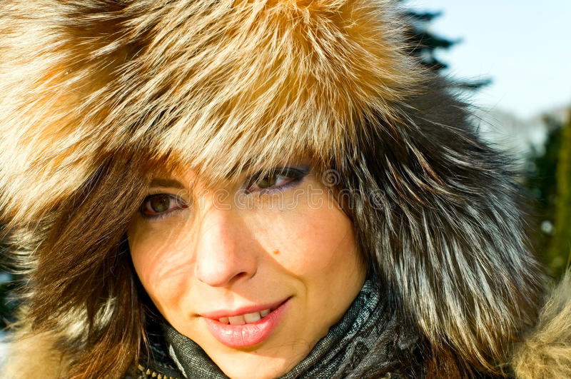 Brunette girl in fur-cap royalty free stock photo