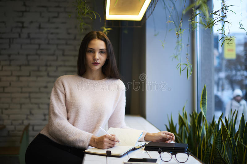 The brunette girl in glasses performs daily work of production necessary to produce offer and sell desired services. Confident female owner of trading royalty free stock image