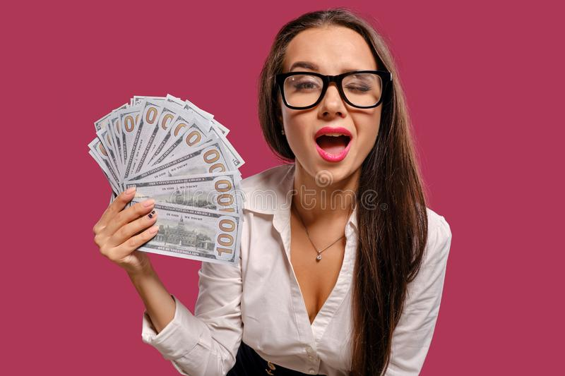 Brunette girl in glasses, wearing in a black short skirt and white blouse is posing holding a fan of hundred dollar. Atractive brunette female with a long hair stock images