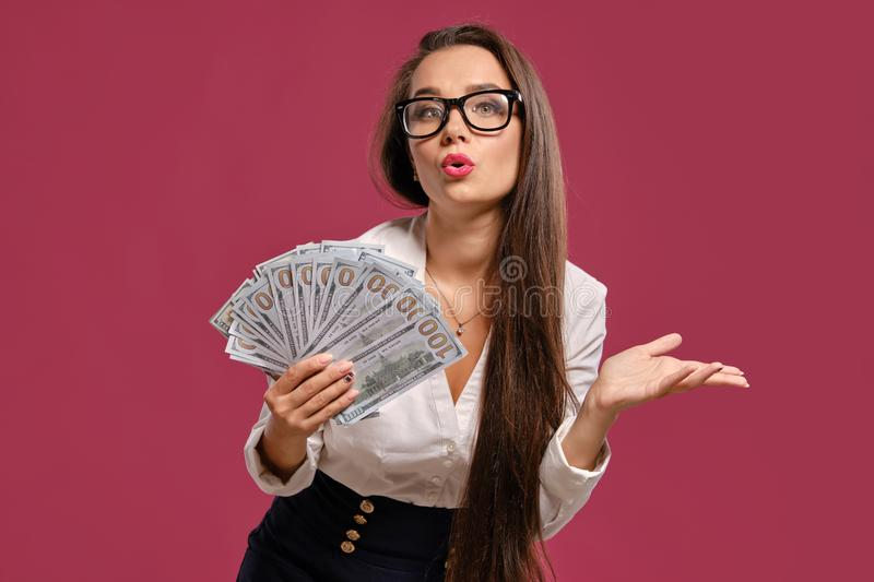 Brunette girl in glasses, wearing in a black short skirt and white blouse is posing holding a fan of hundred dollar. Atractive brunette maiden with a long hair stock images