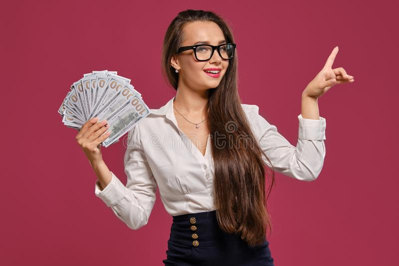 Brunette girl in glasses, wearing in a black short skirt and white blouse is posing holding a fan of hundred dollar. Attractive brunette lady with a long hair stock photography