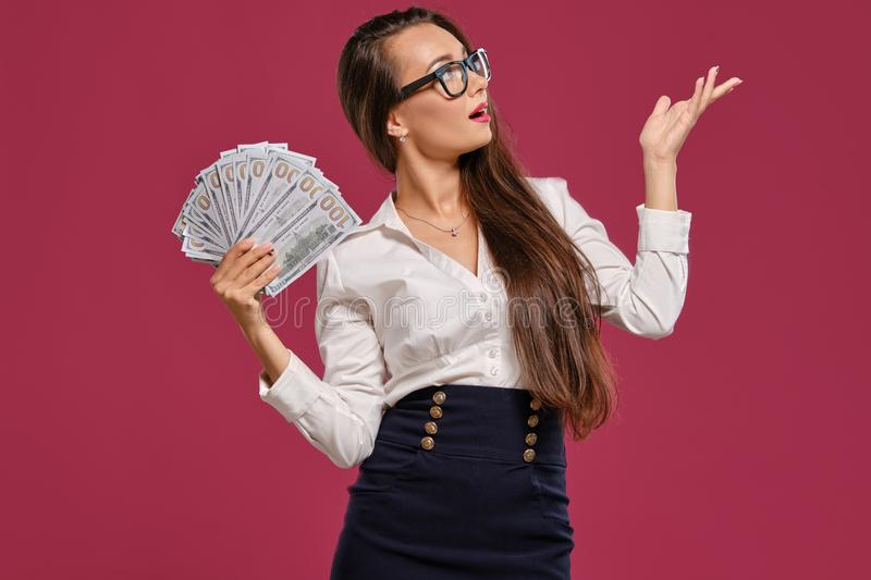 Brunette girl in glasses, wearing in a black short skirt and white blouse is posing holding a fan of hundred dollar. Attractive brunette girl with a long hair stock images