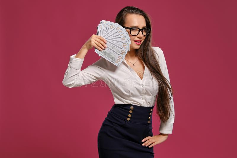 Brunette girl in glasses, wearing in a black short skirt and white blouse is posing holding a fan of hundred dollar. Attractive brunette maiden with a long hair royalty free stock images