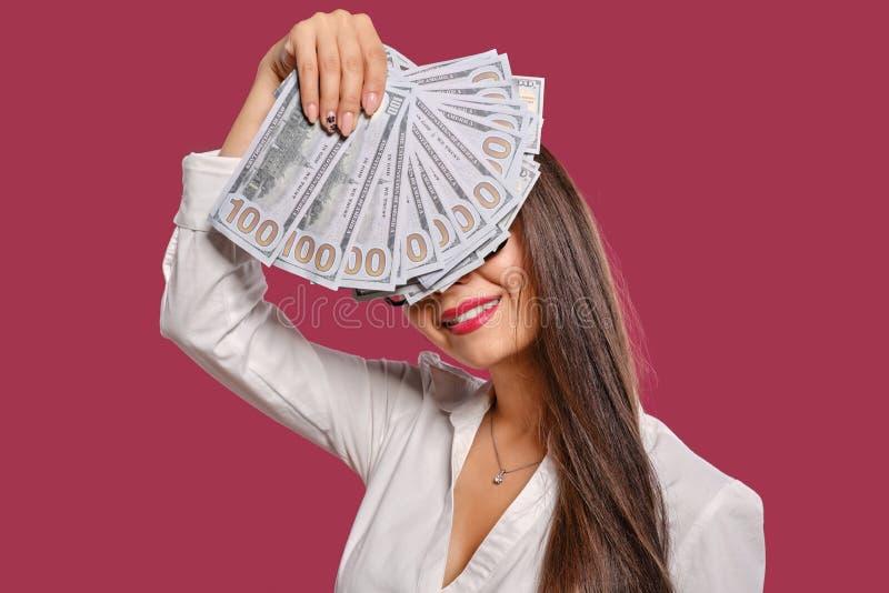 Brunette girl in glasses, wearing in a black short skirt and white blouse is posing holding a fan of hundred dollar stock images