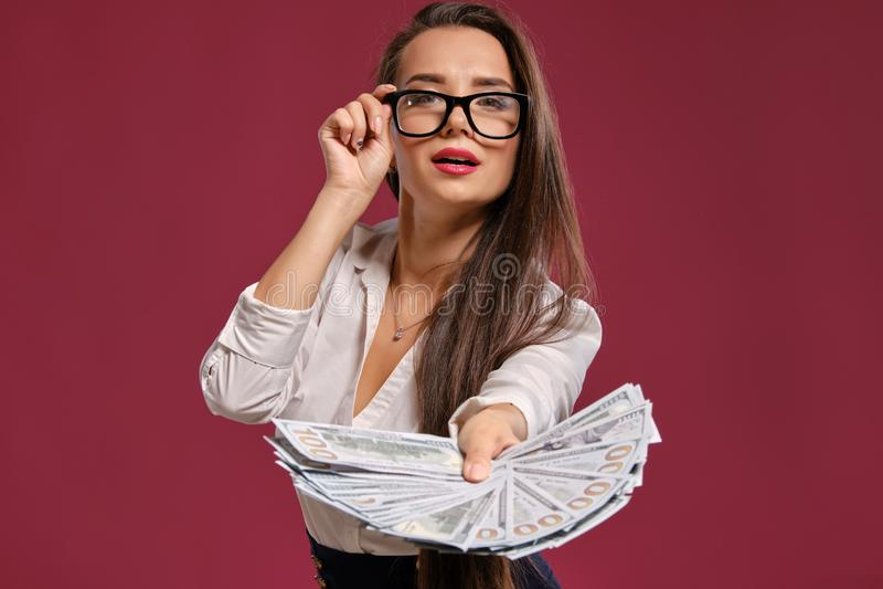 Brunette girl in glasses, wearing in a black short skirt and white blouse is posing holding a fan of hundred dollar. Lovely brunette female with a long hair royalty free stock image